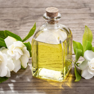 Gardenia essential oil on glass bottle with dropper on wooden table